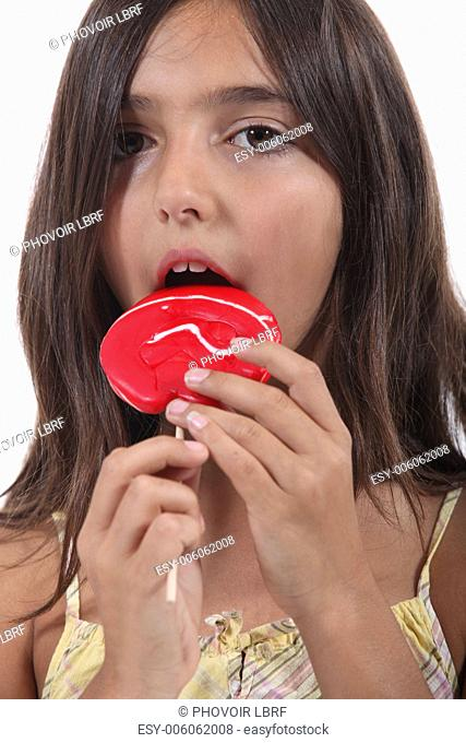 Young girl eating a red lollypop