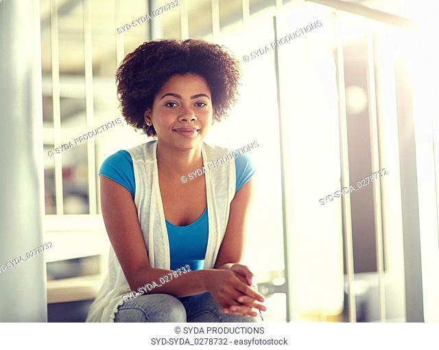 happy african student girl sitting on stairs