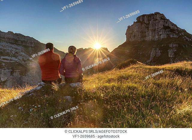 europe, Italy, Veneto, Agordino. Couple of trekkers sitting admiring the sunset near the bivouac Bedin at the First Pala di San Lucano, Dolomites
