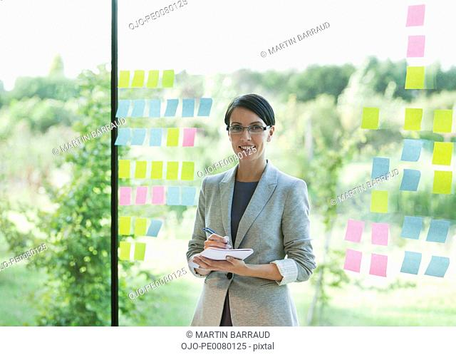 Portrait of confident businesswoman at window with adhesive notes