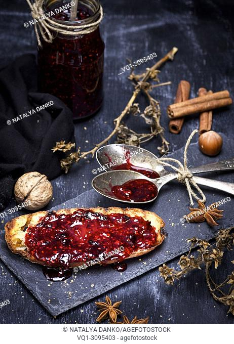 toast of white wheat bread smeared with raspberry jam on a black board, next to a jar of jam