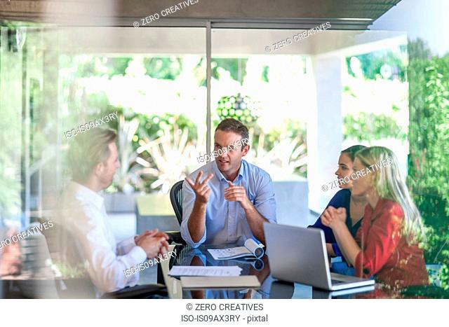 Male and female designers meeting at conference table in design office