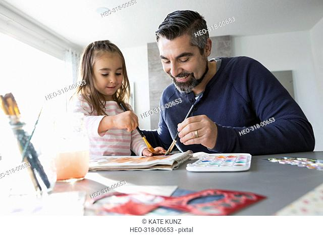 Father and daughter painting at dining room table