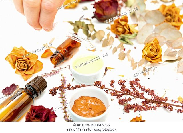 Aromatic botanical cosmetics. Dried herbs flowers mixture, facial mud clay mask, oils, applying brush. Holistic herbal skincare beauty hack