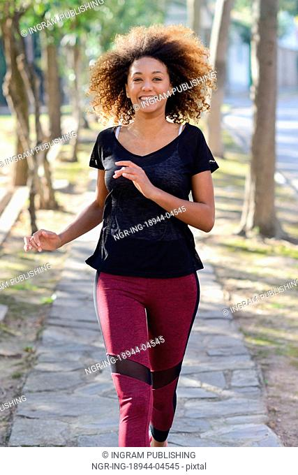 Running woman. Black Female Runner Jogging during Outdoor Workout in a Park. Beautiful fit Girl. Fitness model outdoors. Weight Loss
