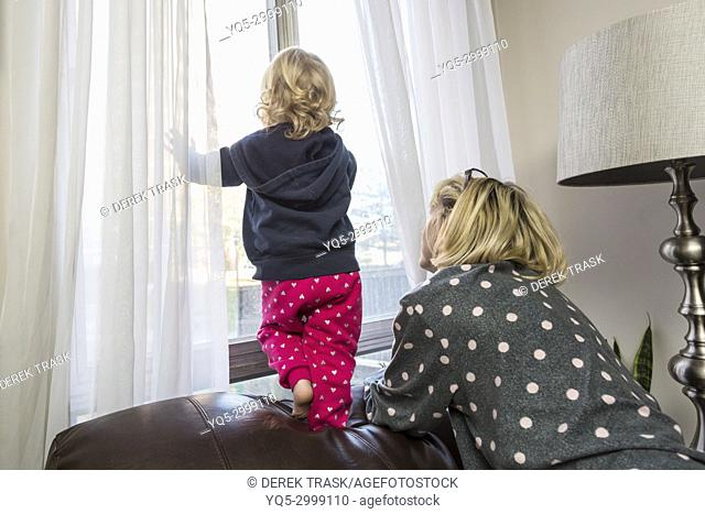 mother and child looking out window child is at risk of falling