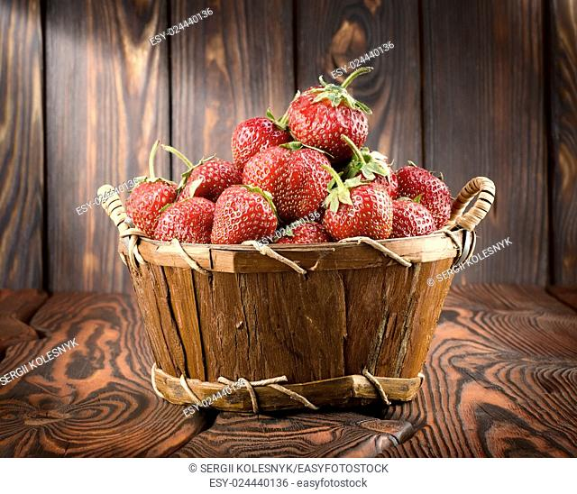 Strawberries in a basket on a wooden background