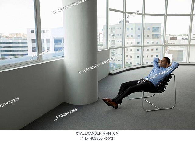 Singapore, Businessman sitting in chair in empty office