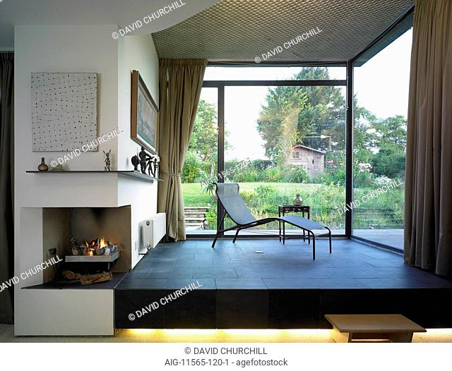 Modern house extension with raised wooden seating area, corner curtained picture window, corner lit fireplace and view of garden