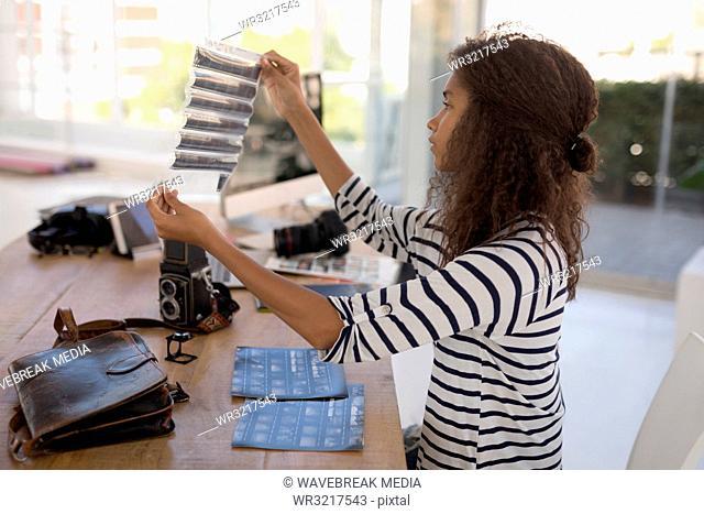 Photographer checking photo negatives at desk