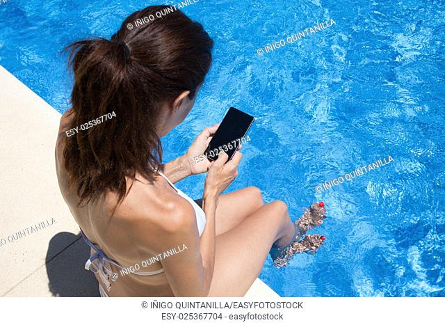 brunette woman wearing white bikini sitting on the edge of pool using mobile phone touching blank screen with blue water behind