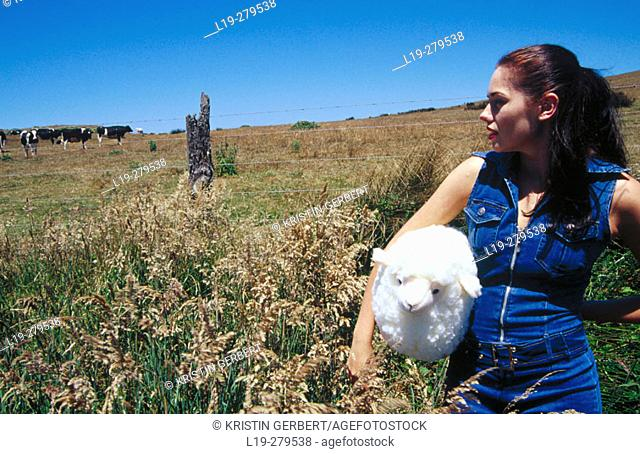 young woman holding sheep in field