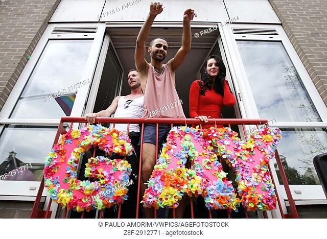 Revelers on the balcony in the Prinsengracht canal participating in the Amsterdam Canal Parade during Amsterdam Gay Pride on August 5 , 2017 in Amsterdam