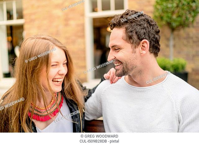 Happy young couple on park bench