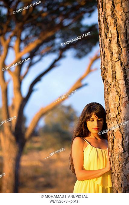 Sad woman leaning against a tree