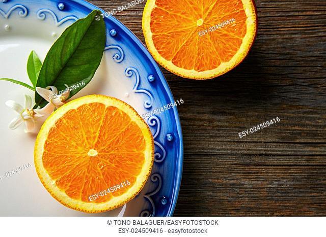 Cut half open orange fruit with orange flower on wooden table