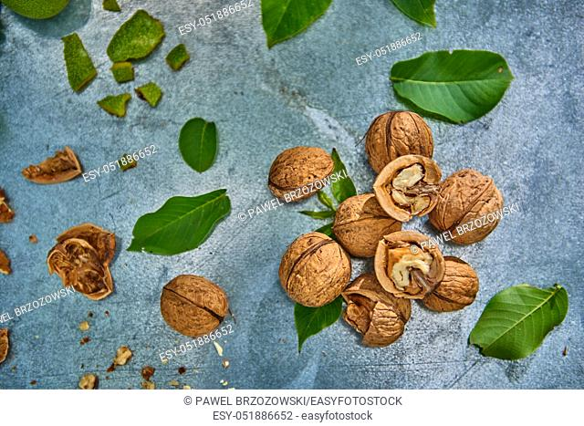 Walnuts and leaves on gray background