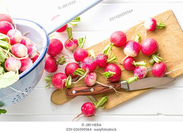 Fresh radishes on old cutting board with knife. Healthy vegetable red radishes