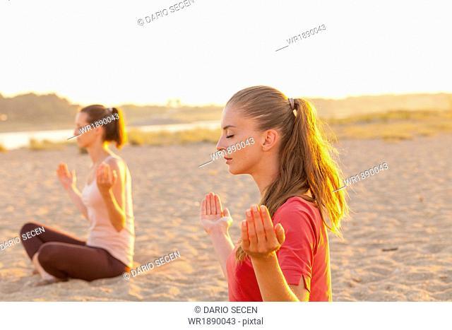 Women practising yoga on beach, lotus pose, hands raised
