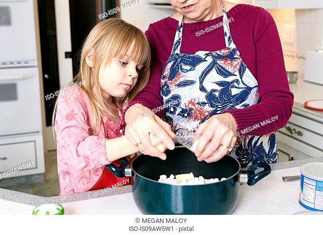 Girl and grandmother measuring salt for saucepan