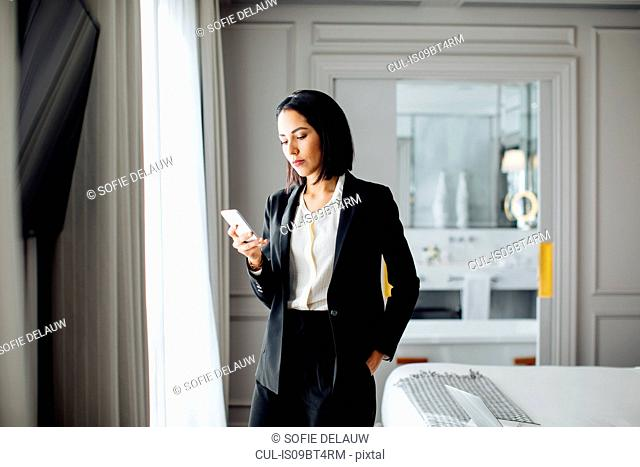 Businesswoman using smartphone in suite
