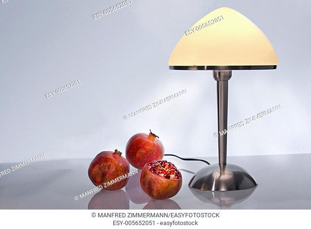Still life with lamp and pomegranates