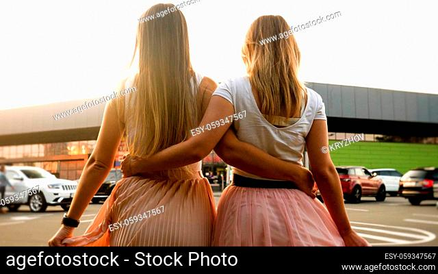 Rear view image of two girls hugging and walking on city street at sunset