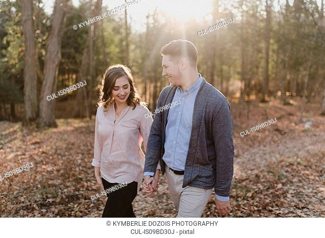 Young couple holding hands, walking in forest, Ottawa, Canada