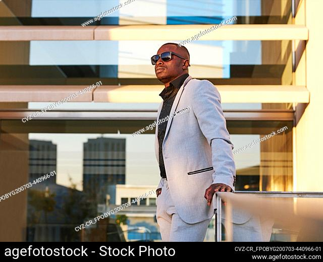 African-American man in a fancy suit enjoying the sunset outside the office