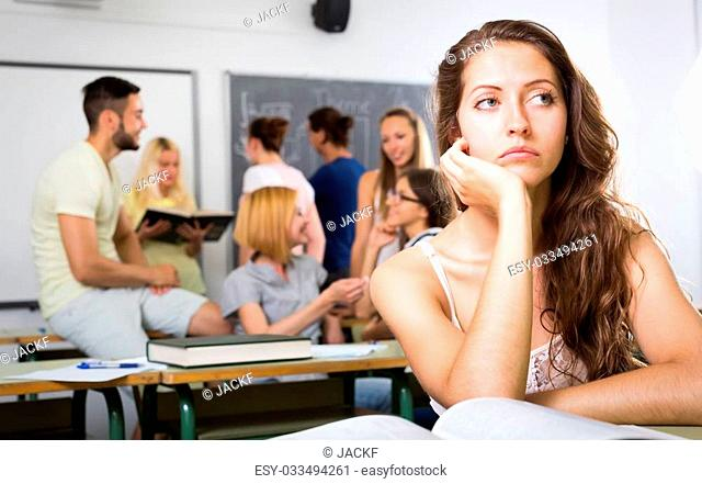 Bored lonely female student sitting in classroom at her desk