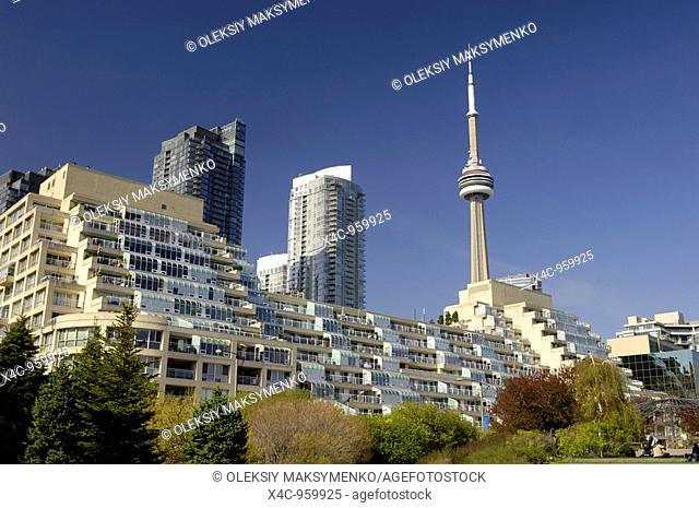 Luxury condos with tiers of terraces and roof gardens in Toronto with CN tower over rich blue sky in the background Real estate concept Toronto Ontario Canada...