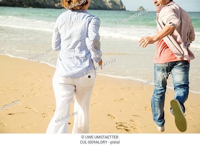Mature couple running on beach, Camaret-sur-mer, Brittany, France