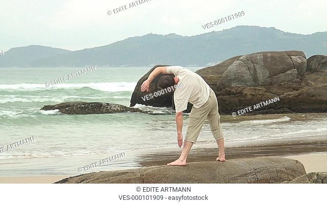 HD 1080i: Mann macht Dehnungsübungen auf einem Fels am Strand