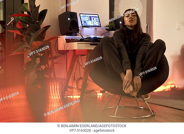 attractive woman sitting on chair next to music loudspeakers and producer pult, music producer