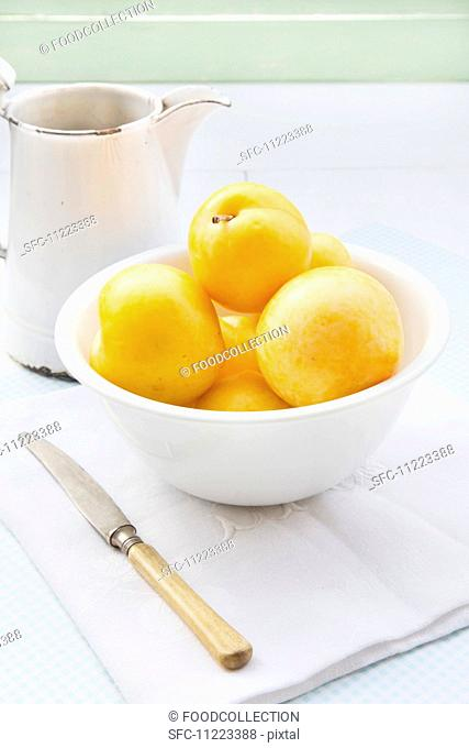 Yellow plums in a white bowl