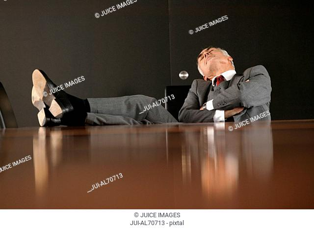 Executive with his feet up on the boardroom table