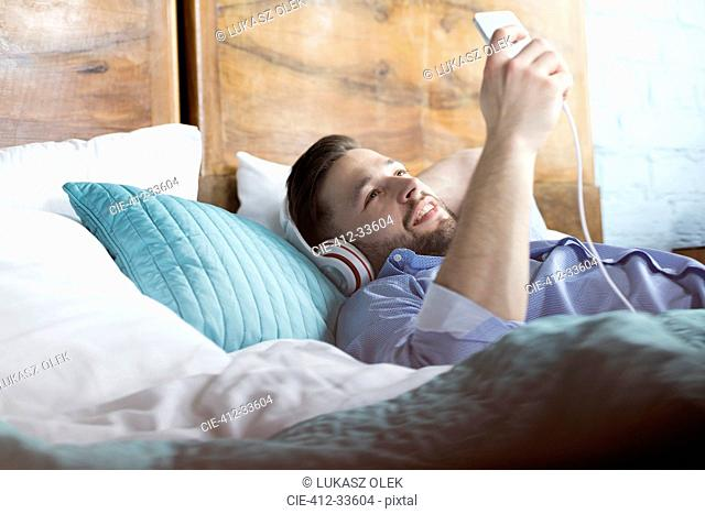 Man listening to music with headphones and mp3 player laying on bed