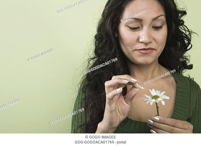 Woman plucking petals from flower
