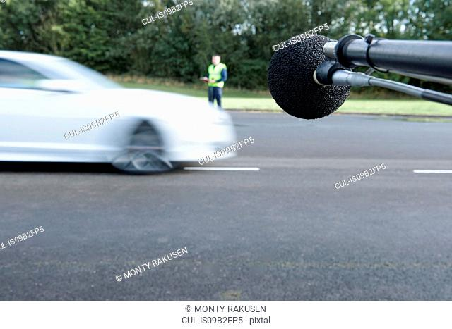 Engineer measuring vehicle sound level at test track