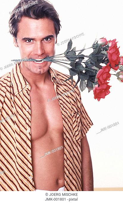 Portrait of a young man, 20-25 25-30 30-35 years old, dark-haired, masculine and beautiful, holding red roses between the teeth