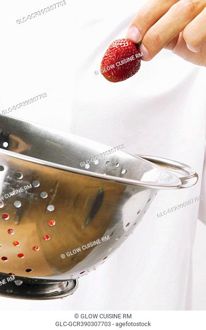 Man holding strawberries in a colander