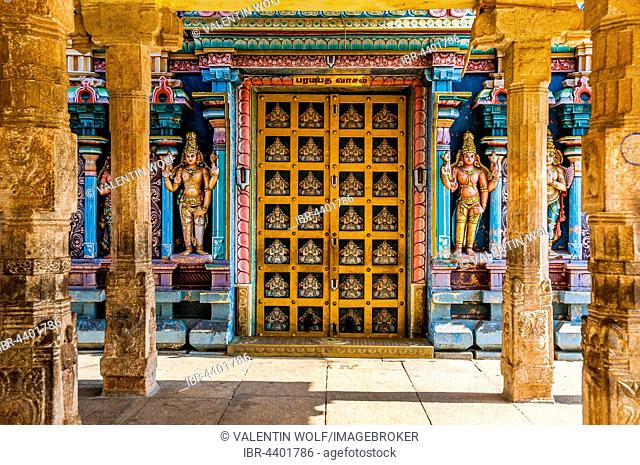 Colorful interior of Hindu temple with decorated door and pillars, temple city Srirangam, Iruchirappalli District, Tamil Nadu, India