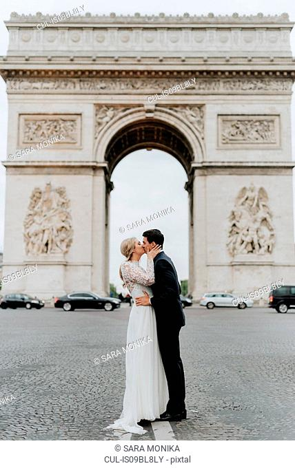 Bride and bridegroom kissing, Arc de Triomphe in background, Paris, France