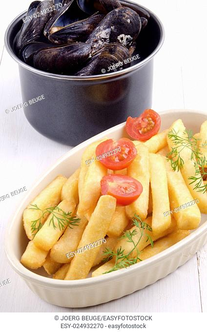 cooked mussel and french fries in a bowl with tomato and dill, Belgian dish