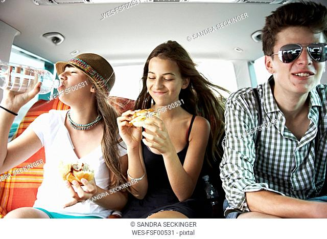 Three teenage friends having a snack in car