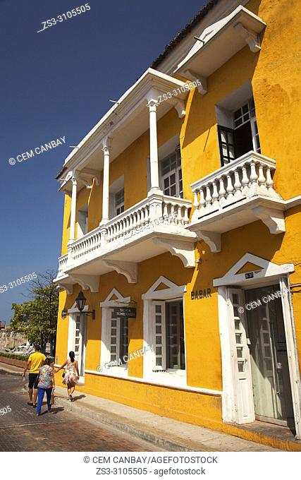 Tourists near the colorful colonial buildings with balconies at the historic center, Cartagena de Indias, Bolivar Region, Colombia , South America