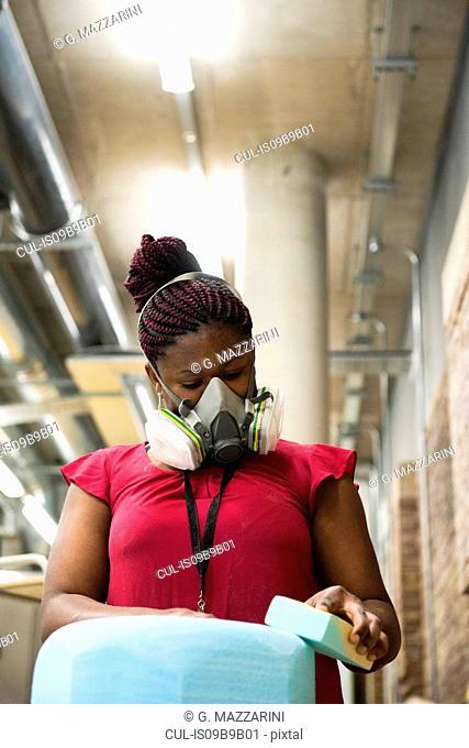 Woman in art studio wearing protective mask sanding object