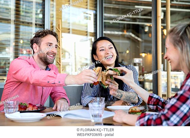 Happy friends having lunch in a cafe