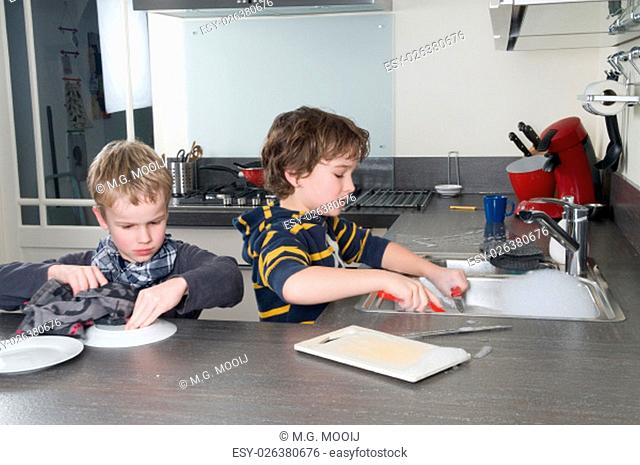 Two boys doing the dishes in a modern kitchen