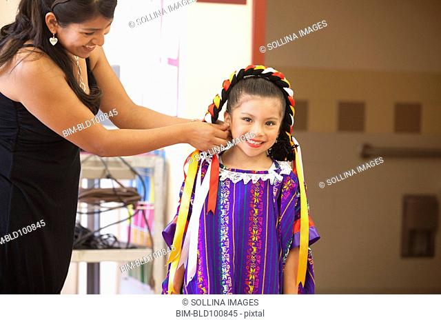 Hispanic mother helping daughter with festive costume